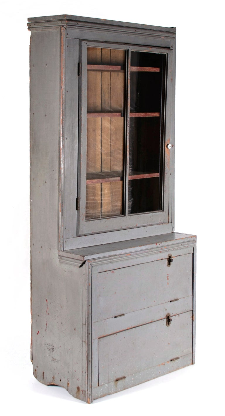 NARROW, MAKE-DO PENNSYLVANIA CUPBOARD IN OLD GREY PAINT OVER AN EARLIER RED, WITH A GLAZED DOOR AND TWO UNUSUAL DROP-DOWN DOORS, CA 1890:  Unusual country step-back cupboard with plank sides on shallow, half-moon, boot-jack feet; a make-do form,