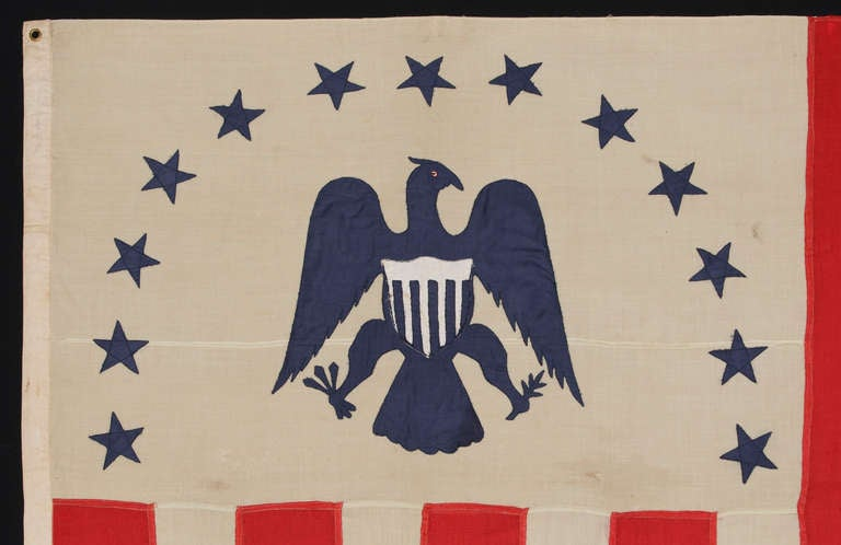 RARE REVENUE CUTTER SERVICE FLAG WITH A BLUE EAGLE AMID AN ARCH OF 13 BLUE STARS, ON A WHITE FIELD, AND AN UNUSUAL COUNT OF 17 VERTICAL RED AND WHITE STRIPES, CA 1880-1895:  United States Revenue Cutter Service flag, made in the period between 1880