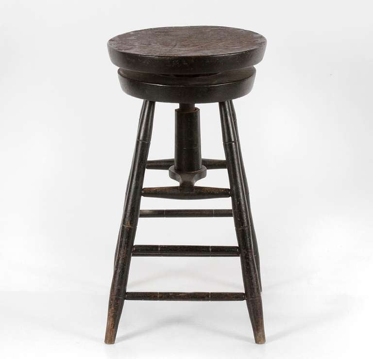 RARE SWIVELING WINDSOR STOOL IN BLACK PAINT, CA 1820-1840:  This unusual Windsor chair is in the form of a medium height stool with a round, swiveling seat. The turnings are in the bamboo style indicative of the 1st quarter of the 19th century,