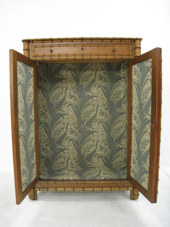 Faux Bamboo Early 20th Century Armoire with Upholstered Interior and Upholstered Drawer.