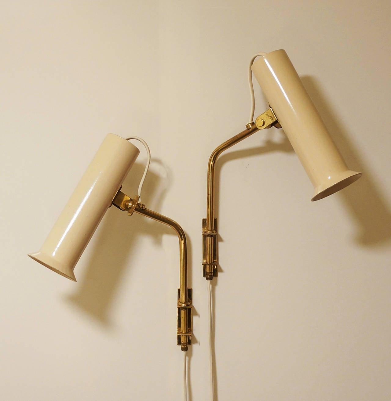 Tapio Wirkkala.  Reading lamps.  Idman, Finland, 1950s  Solid brass and painted metal. Measures: Height circa 30 cm, width circa 20 cm.  Both lamps impressed with manufacturer's label Idman as well as both wall mounts.  Shade and stem adjustable
