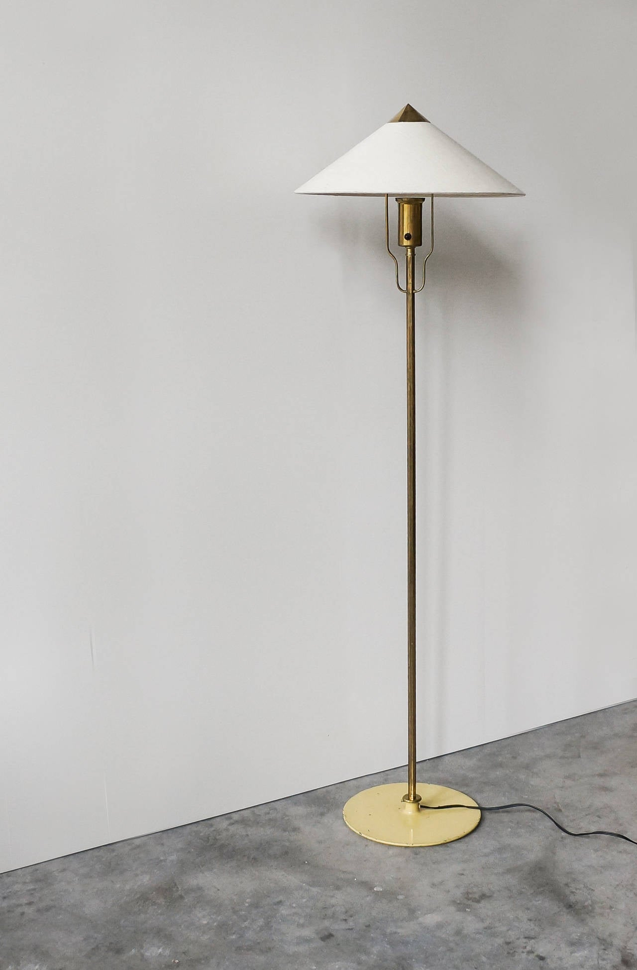 Paavo Tynell floor lamp, model 5762.  Early example by Taito Oy, Finland, late 1940s.  Brass, painted cast iron base, wool fabric shade. Measures: Height circa 142 cm, width 43 cm, depth 43 cm.  Impressed with manufacturer's mark