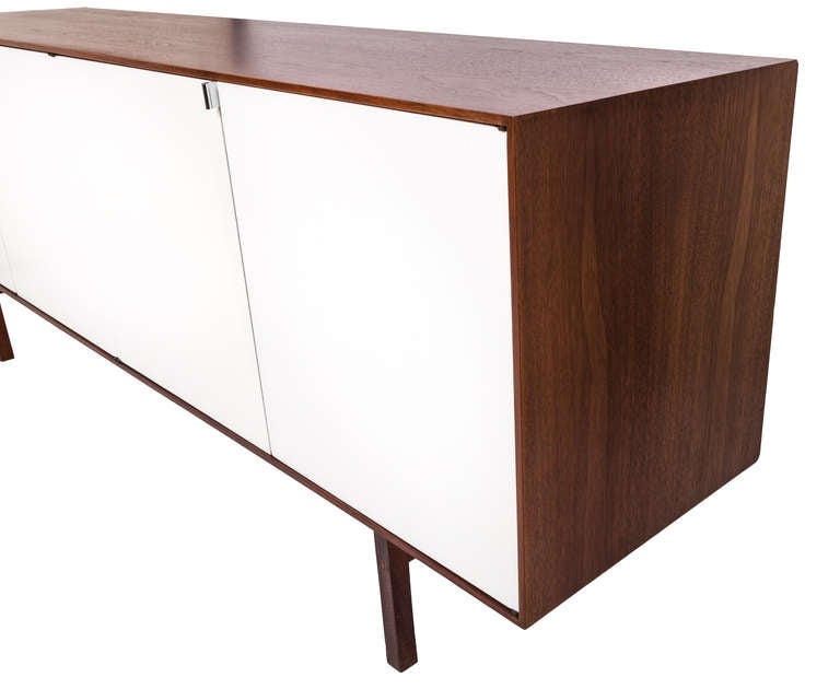 Florence Knoll designed credenza/cabinet for Knoll.   USA, 1950s  Features dark walnut exterior and legs with white lacquered doors stainless drawer pulls.   Very good condition with original label attached