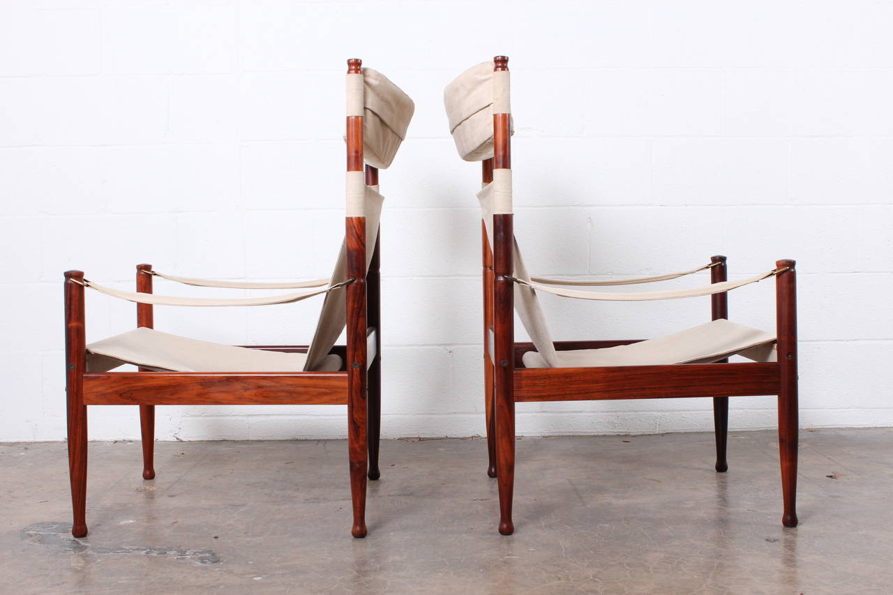 A pair of high back rosewood and canvas safari chairs designed by Niels Eilersen.