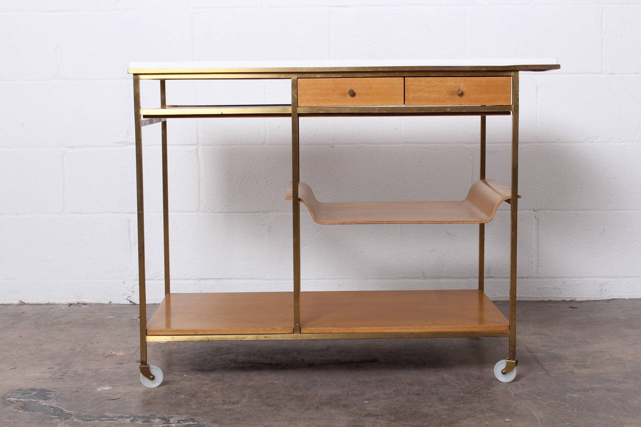 A brass bar cart in bleached mahogany with Vitrolite top. Designed by Paul McCobb for Calvin.