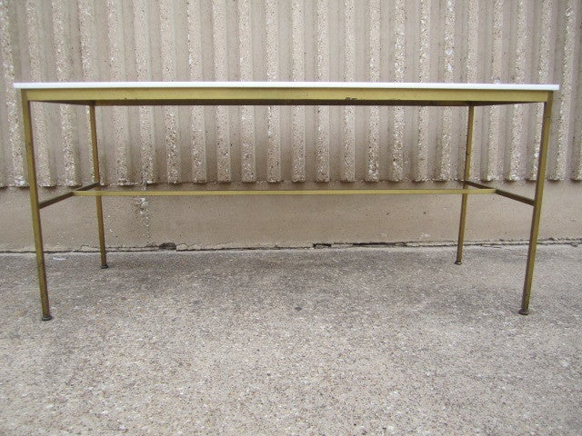 A brass console table with Vitrolite top designed by Paul McCobb for Calvin.