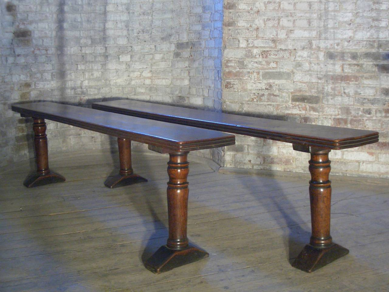 A sleek, sturdy pair of long, narrow benches, the thick, reeded top supported by turned legs on simple shoe-feet.