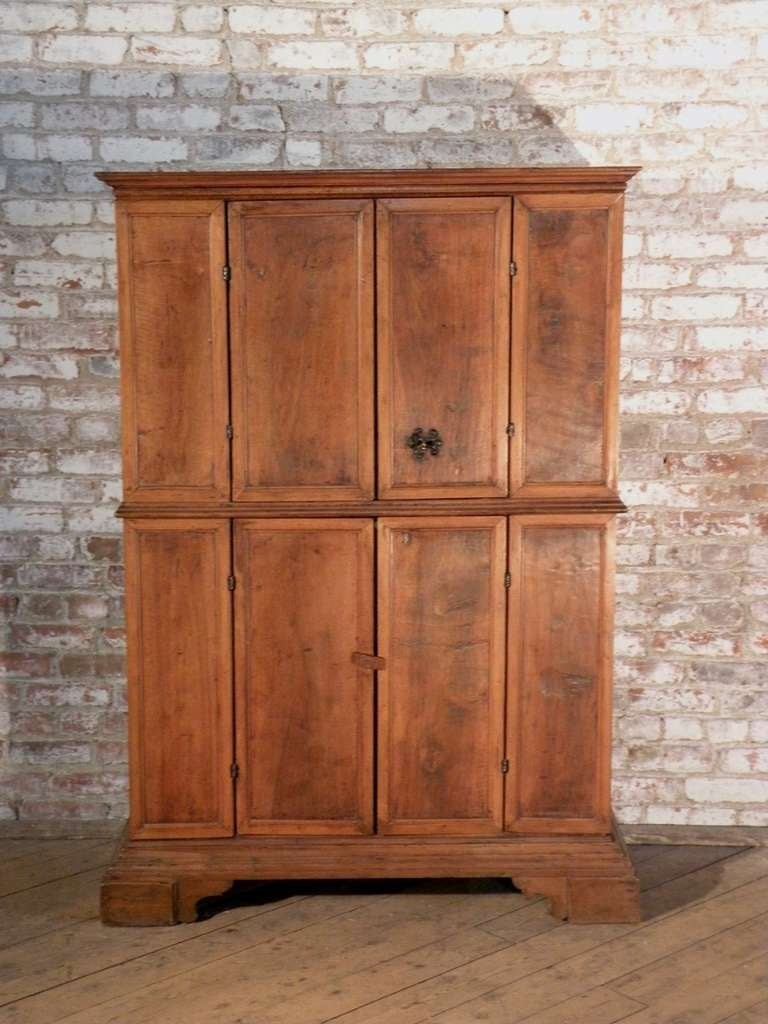 Tuscan cabinet or bookcase of unusual diminutive proportions and wonderful light honey color. The four doors opening to shelved interiors, on bracket feet.