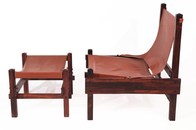 Rare Jorge Zalszupin rosewood and leather sling chair and ottoman, circa early 1960s. This example has an exquisitely grained stacked rosewood frame with hand-stitched original caramel leather sling and seat. Price is for the chair and ottoman.