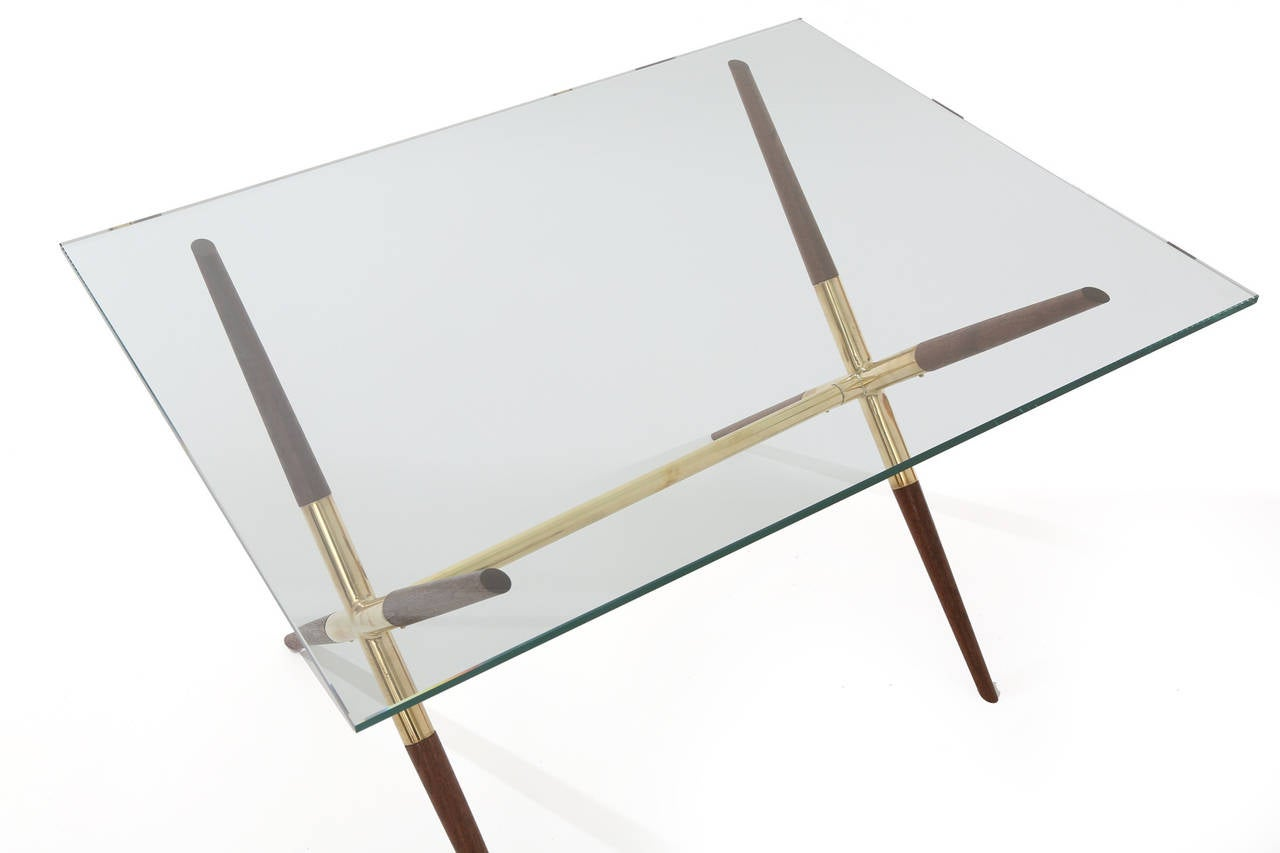 Tapered solid walnut and polished brass cocktail or occasional table from Italy, circa late 1950s. This lovely example has sculptural newly oiled walnut inserts with mirror polished brass frame. Current glass measures: 32