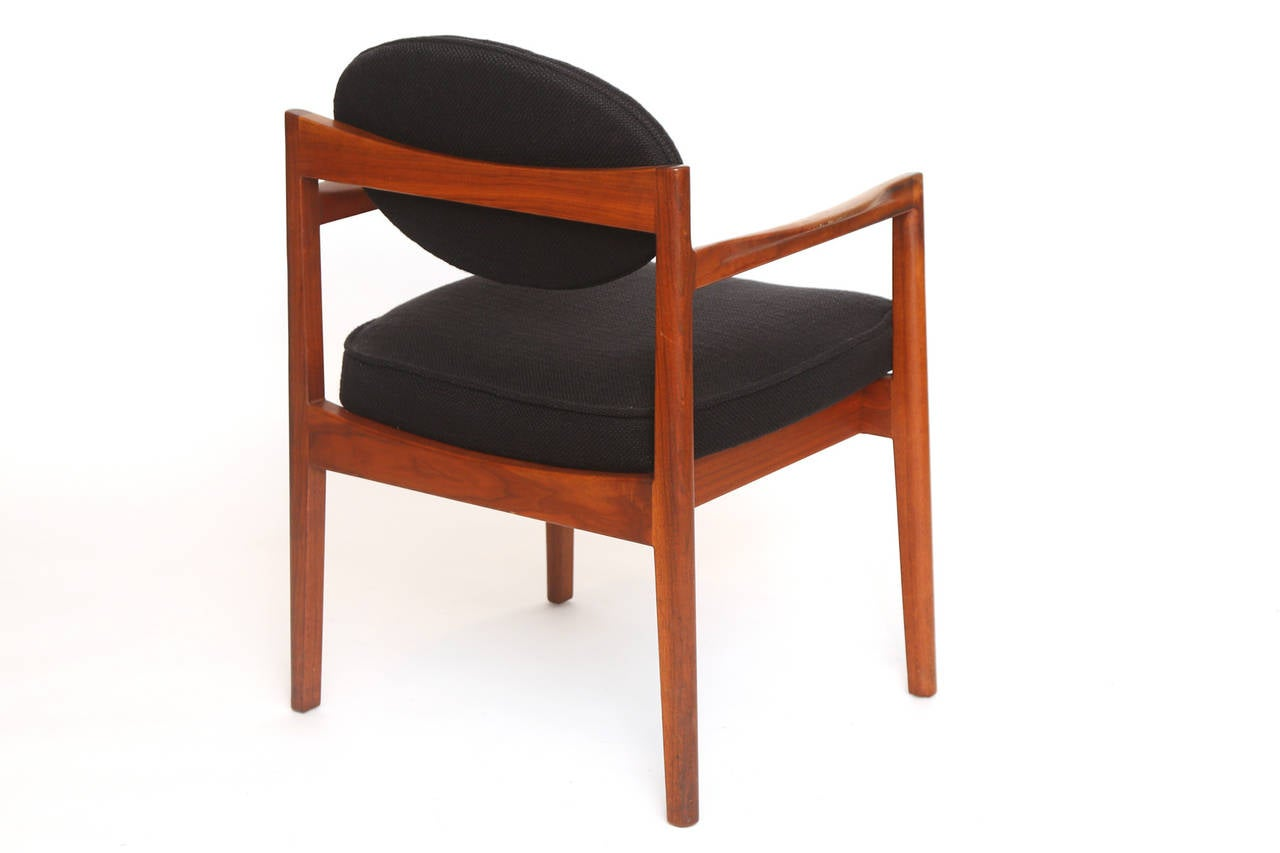 Set of six sculpted walnut and upholstered armchairs by Jens Risom, circa mid-1960s. These examples have solid walnut frames with flared arms and floating backs. They are upholstered in their original black heathered bouclé. Price listed is for the