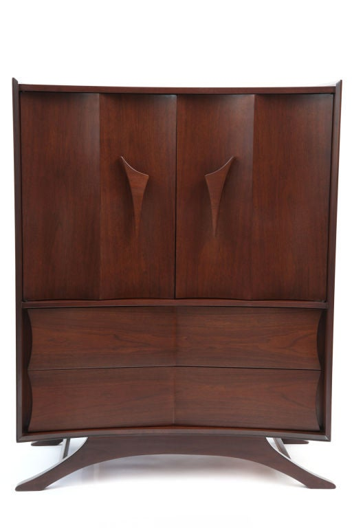 Phenomenal walnut highboy circa early 1960's. This subtly curved example has large free form door pulls 6 drawers for more than ample storage  wonderful curved doors and sculptural splayed legs. Please see our other listings for the matching chest