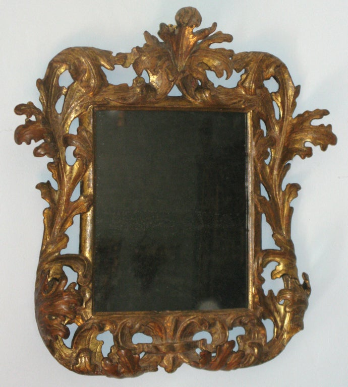 An elaborately carved and gilded baroque mirror at 1stdibs for Gilded baroque mirror