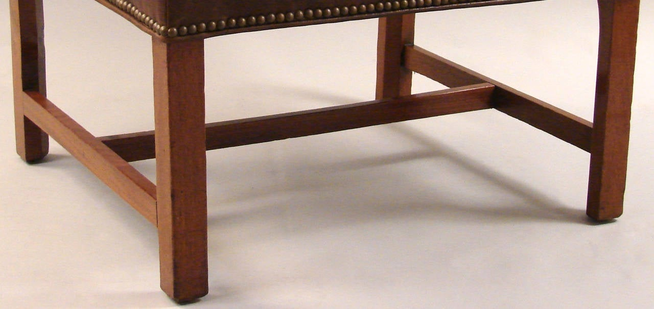 A substantial George III period mahogany stool, now upholstered in brown leather with brass nailhead trim, and an attached cushion resting on straight legs joined by an
