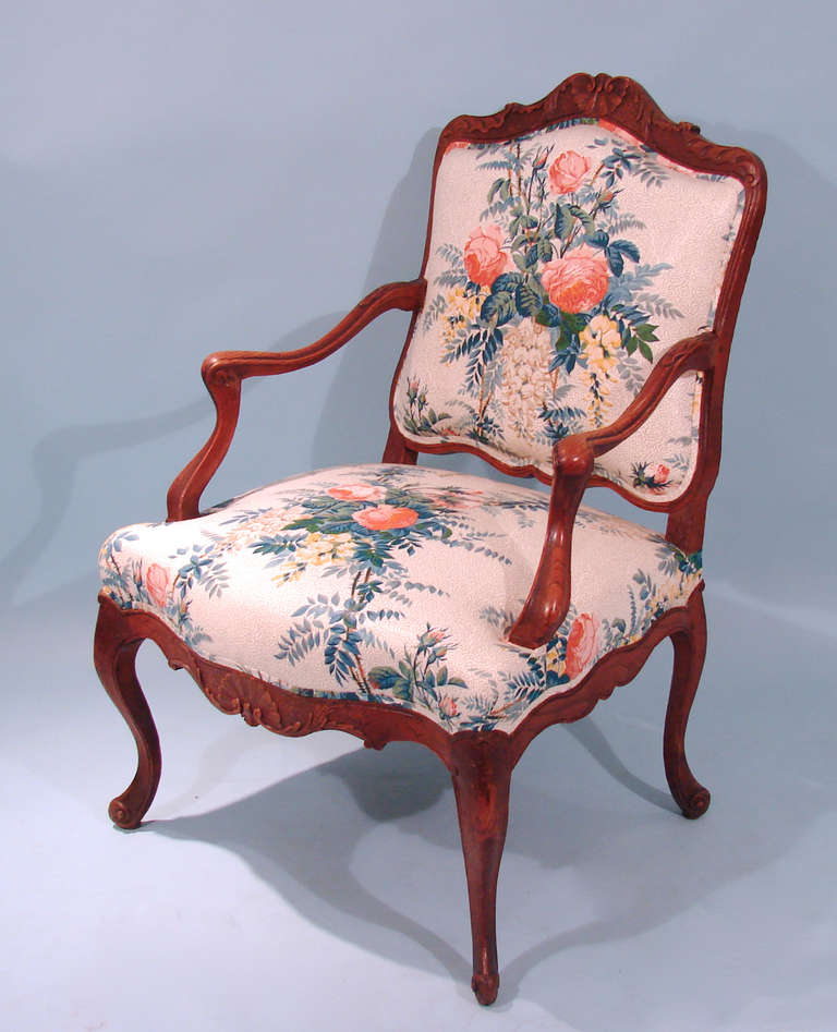 A Louis XV style oak armchair of typical form, the apron with a central shell decoration resting on cabriole legs with scroll feet.