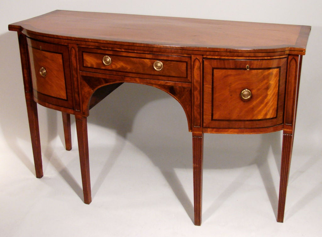 A George III period Hepplewhite design mahogany sideboard, the crossbanded line inlaid top over 2 inlaid drawers and an inlaid cabinet door raised on reeded square tapered legs.