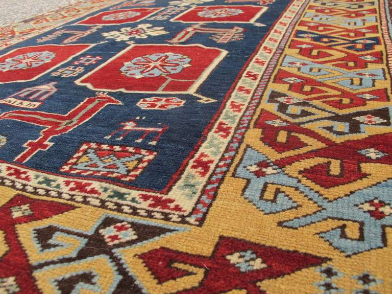 This elegant east Caucasian Kuba rug draws a distinctively Karagashli take on the Classic Caucasian 'afshan' floral design. Curvilinear diamond-pointed foliage painted in deep ruby-red and lined with sea-green and white floats against an indigo