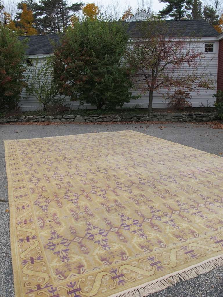 Spanish carpets woven in the early twentieth century, such as this piece, often use designs that hearken back to Spain's medieval Moorish past. With a light palette consisting of a gold ground and tracery in complimentary contrasting violets, the