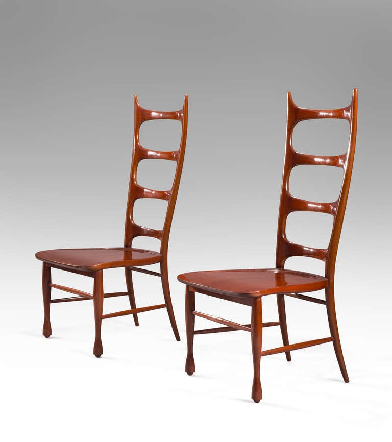 The beautifully carved high back chairs have a sophisticated sculptural quality. The back composed of four lozenge shaped cross braces joined to the curved and pointed uprights, the shaped seat above legs joined by stretchers.  Provenance: Casa