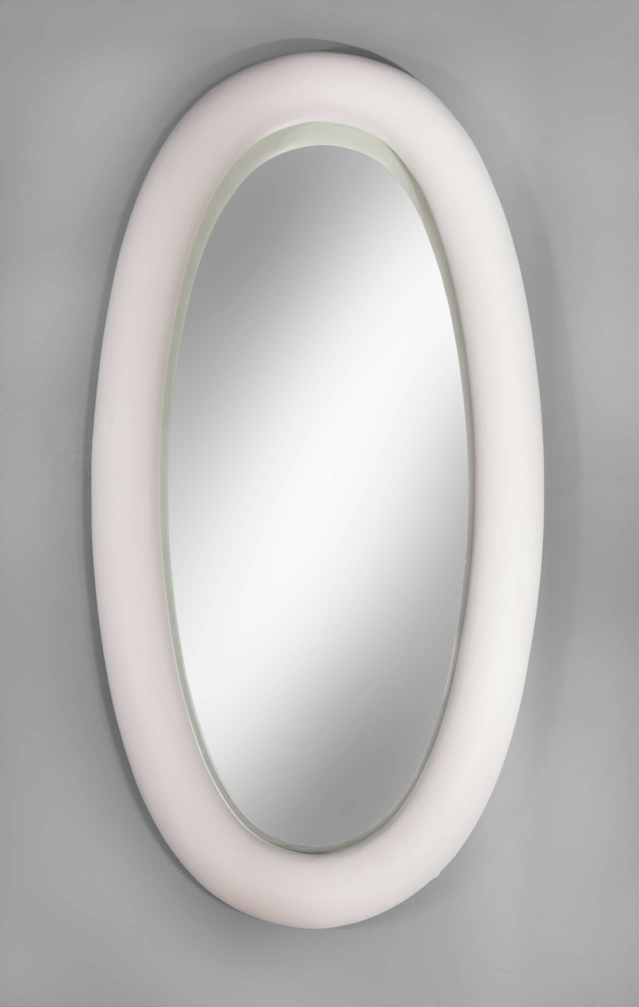 The monumentally scaled and deeply recessed frame of this fantastic piece balances perfectly with the powdery, soft white finish. The massive rounded frame has a delightfully surreal feel about it. The elliptical mirror plate in a rounded wood and