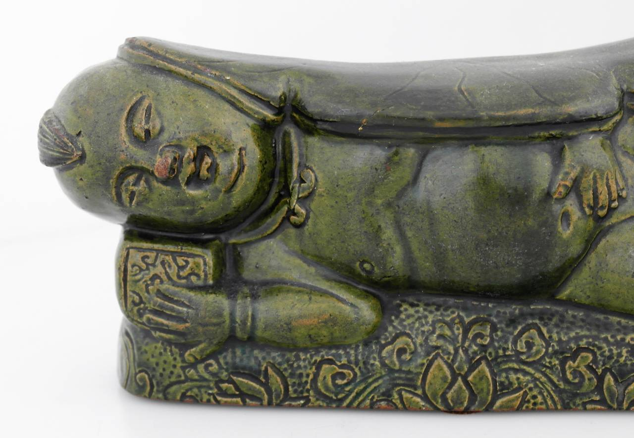 Being offered is a scarce 16th century figural Chinese pillow, green painted example molded into the shape of a reclining subject on a pillow, the headrest in the form of a lotus motif, floral motifs underneath the subject. Due to their scarcity,