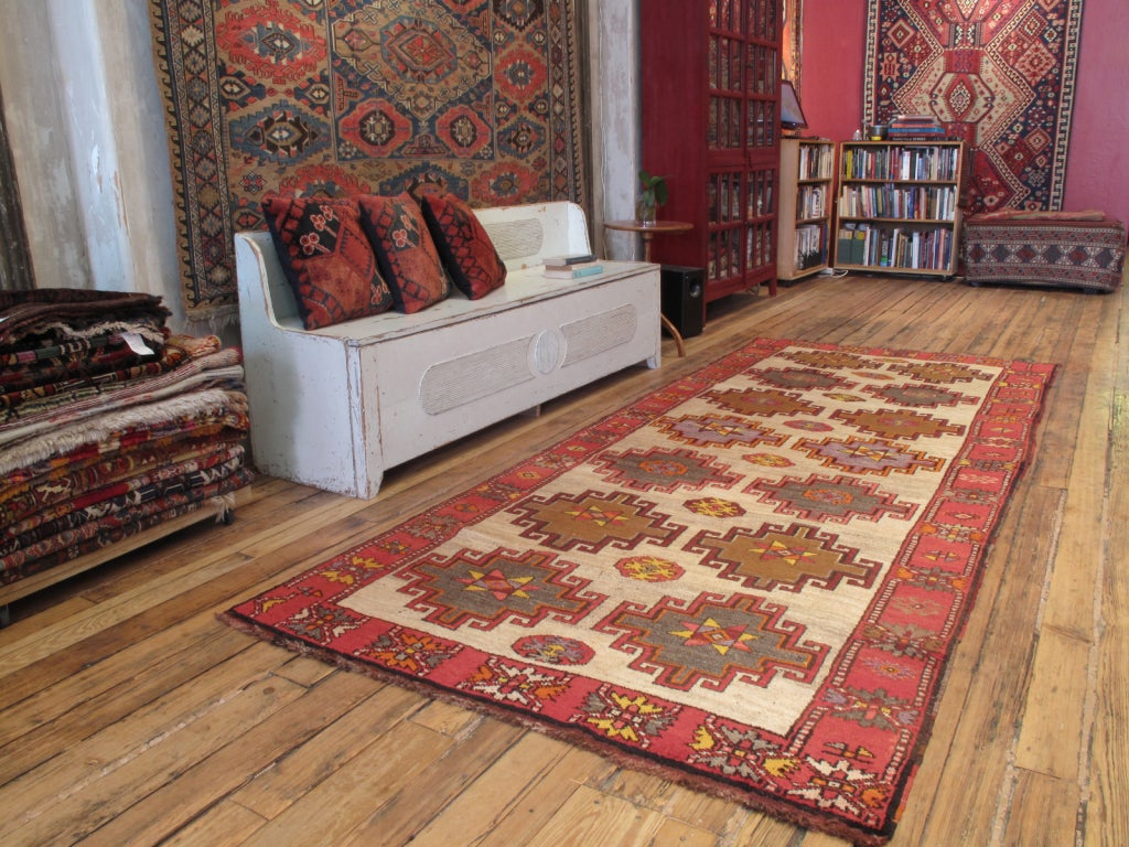 Kurdish long runner rug. Rug has striking tribal emblems on a light camel background. Densely woven rug with soft, high mountain wool.