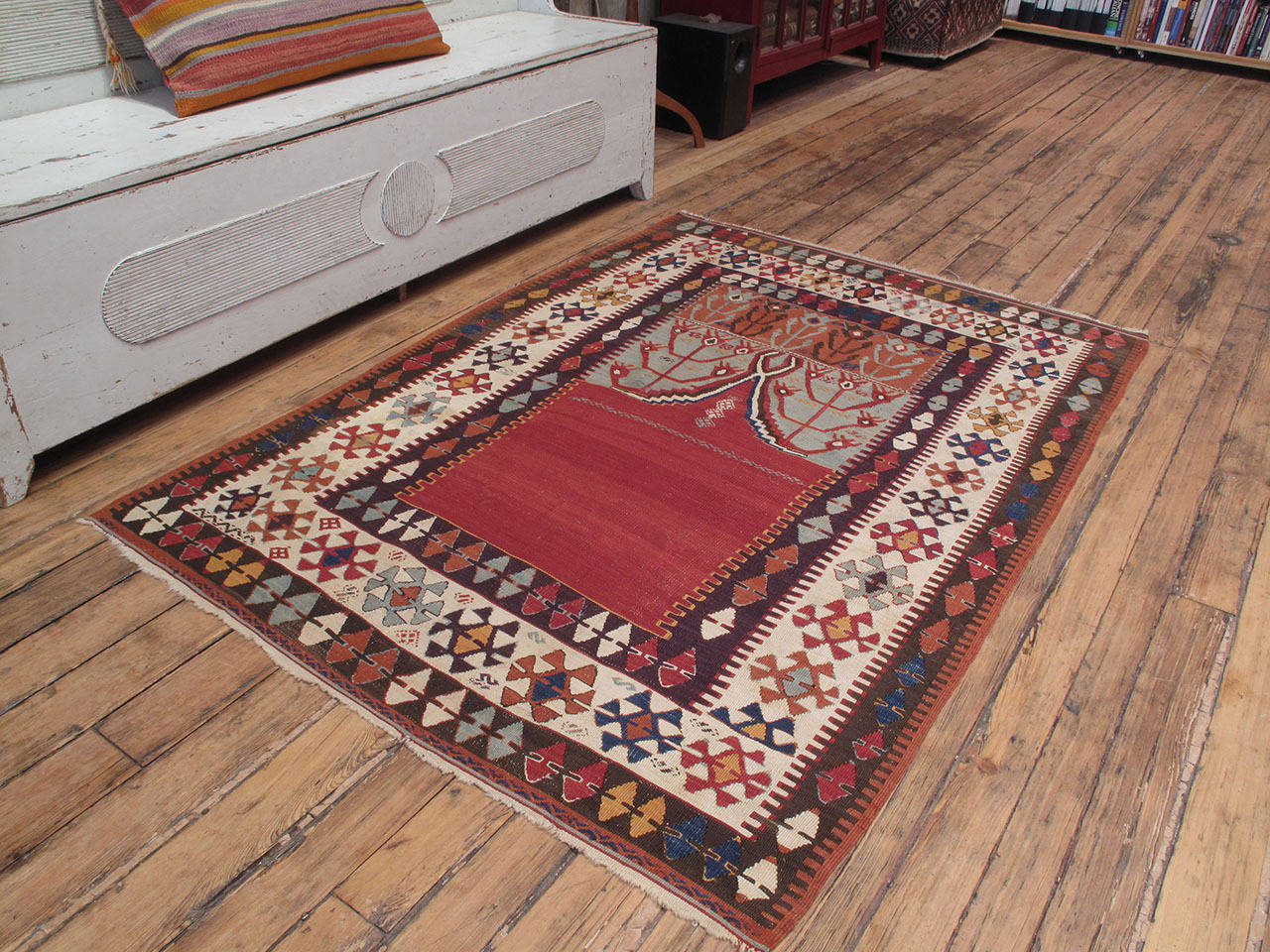 """A beautiful antique Kilim from Central Turkey featuring the ever-popular prayer arch, or """"mihrab,"""" design. The dramatic empty center in red is topped with a stepped arch ending in Horn-like shapes, flanked by highly stylized tulips, the"""