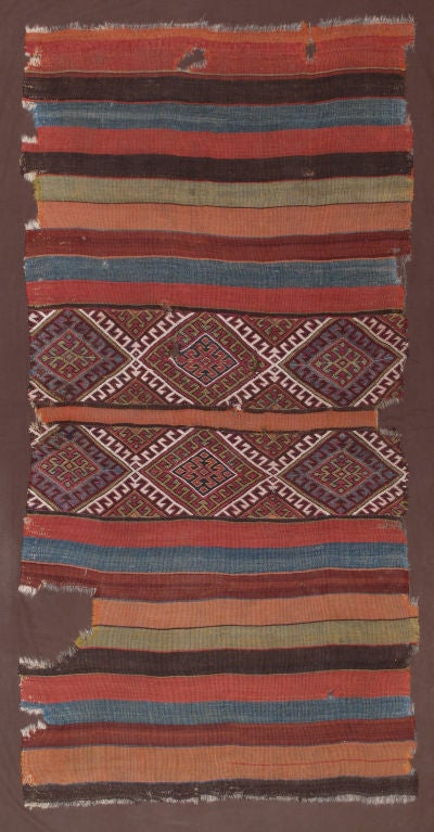 "An antique, nomadic ""grain sack"". A great example of Anatolian kilim art for collectors and connoisseurs of color.(Opened up and professinally mounted on cotton fabric, measuring 50"" by 92"".)"