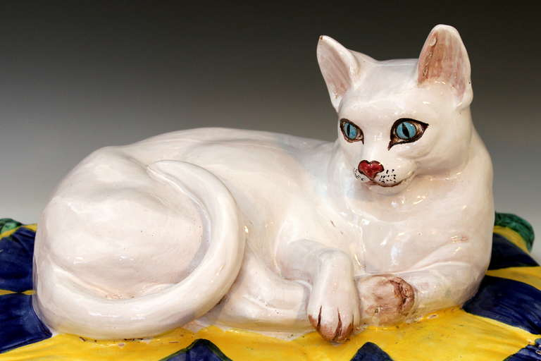 Vintage, large, press molded Italian terra cotta sculpture of a white tabby cat luxuriating on a tasseled pillow in vivid blue and yellow diamond pattern, circa 1960s. Realistically modeled and with striking blue eyes and red nose. Measures: 18