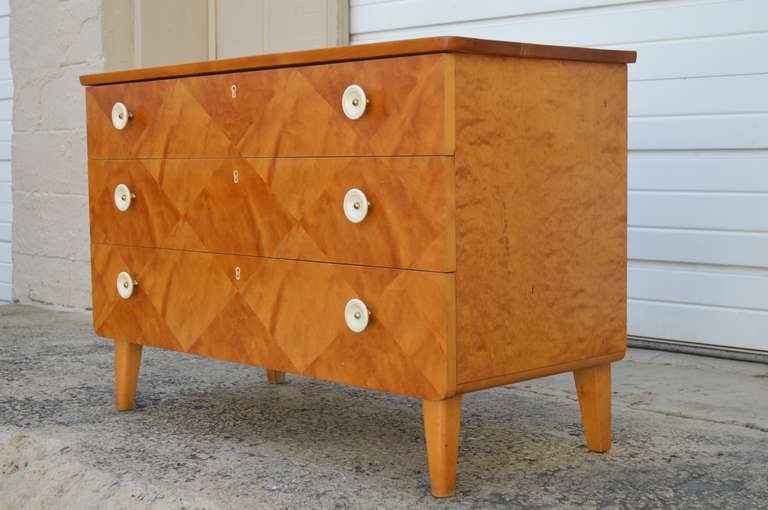 Parquetry chest of drawers rendered in golden flame birch. Beautifully detailed drawers. White round acrylic pulls. Tapered legs. Key included.
