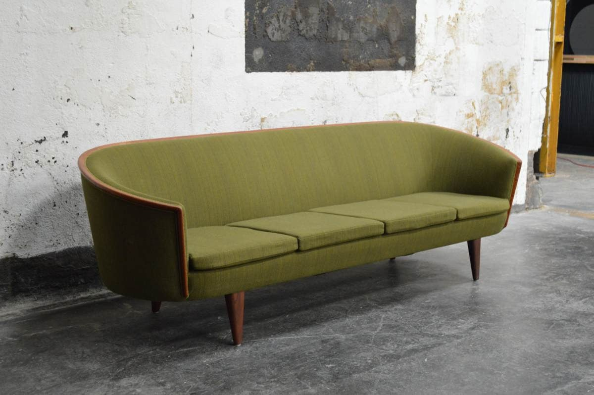 Beautiful and rare Mid-Century long barrel back sofa. This sofa has gorgeous teakwood trim and walnut legs. The back legs set at a bit of an angle along with a graceful pitch give this guy a beautiful Silhouette. Original wool upholstery  Note: