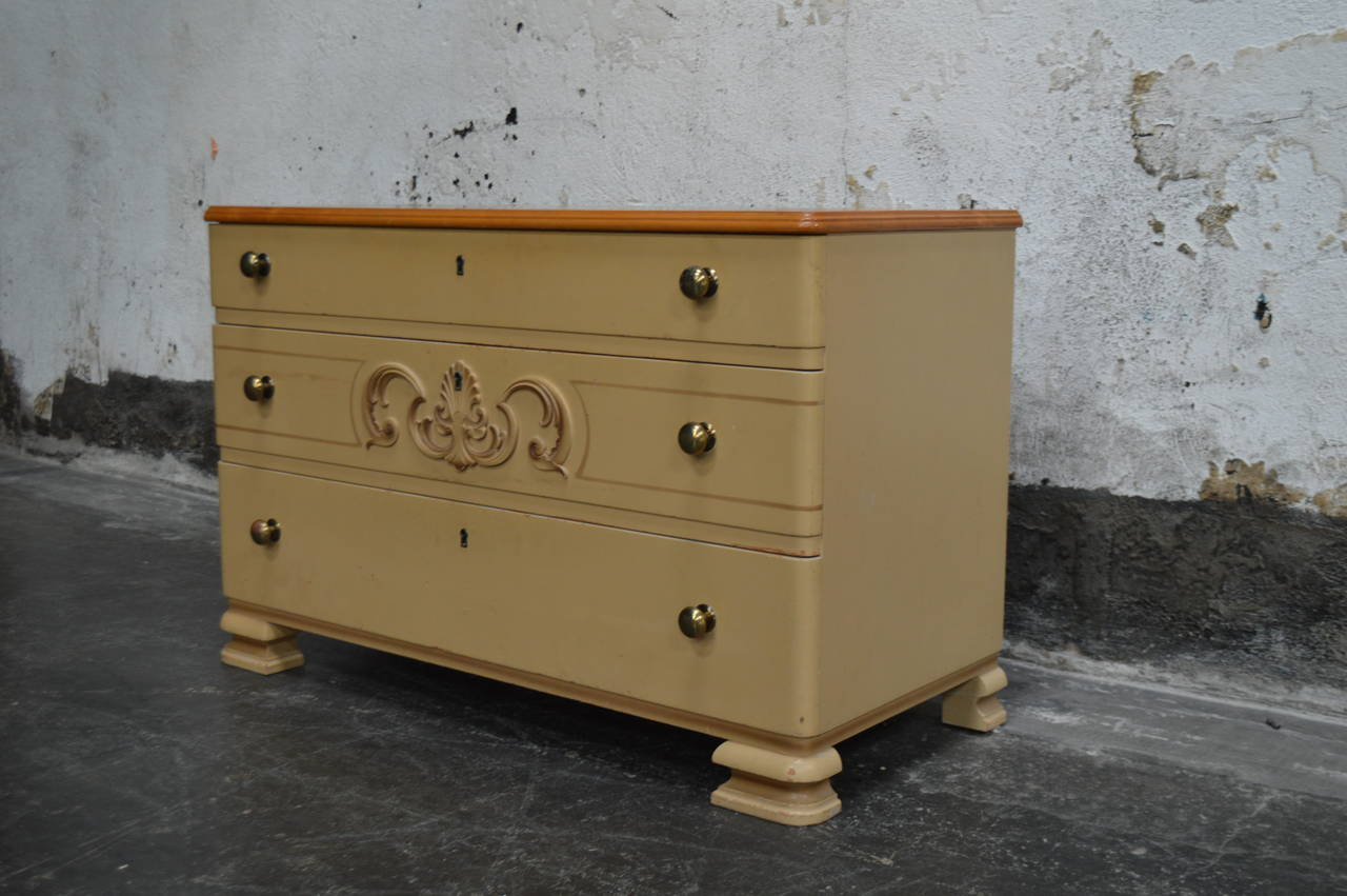 Handsome Art Deco chest of drawers. Original painted finish and golden elm top. Detailed with brass pulls, decorative centerpiece and uniquely shaped legs.