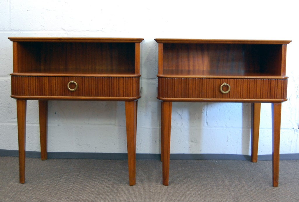 Exceptional pair of ribbon mahogany night stands or end tables with fluted drawers and solid brass ring pulls. These pieces also feature a finished back which is hard to find on pieces style/age.
