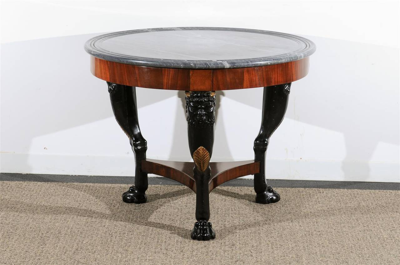 19th century Empire center table raised on painted tri pod base with paw feet, carved faces and gilded acanthus leaves. Grey and white marble top recently restored and French polished, excellent condition.