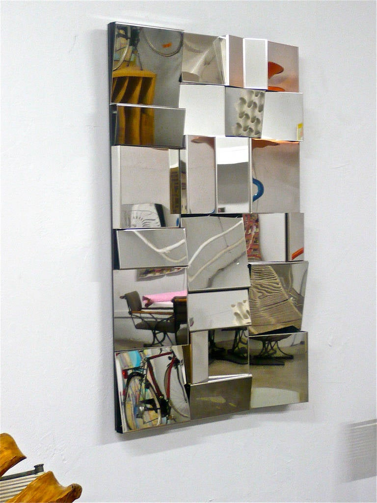 Faceted sections of stainless steel mounted on plywood creating disjointed optics.Similar in style to Neal Small's