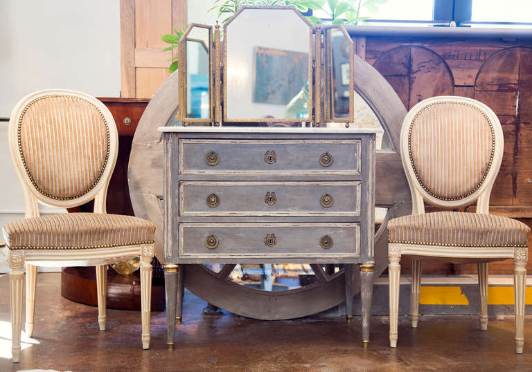 French antique Louis XVI style chest of drawers in solid, hand painted mahogany with white Carrara marble top, bronze hardware, and brass feet on tapered legs.