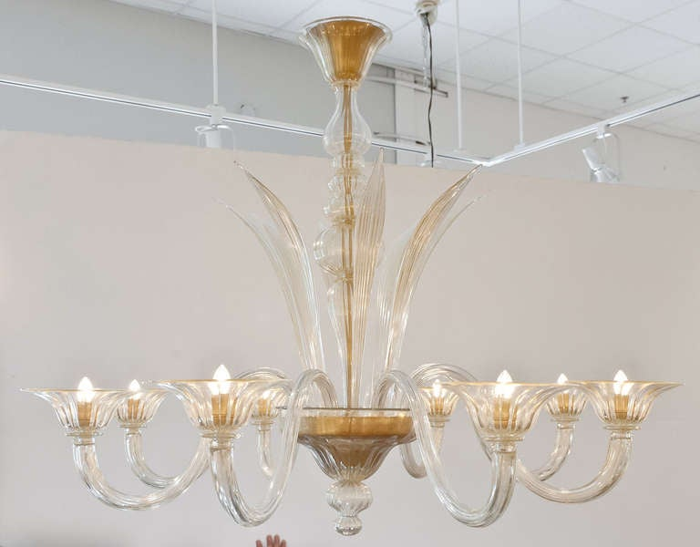 "A beautiful Murano glass chandelier with ""polvera d'oro,"" 23-karat gold flecks, fused in the handblown glass. Eight handblown leaves and branches. Eight candelabra lights, rewired to US standards. The height including the matching glass"