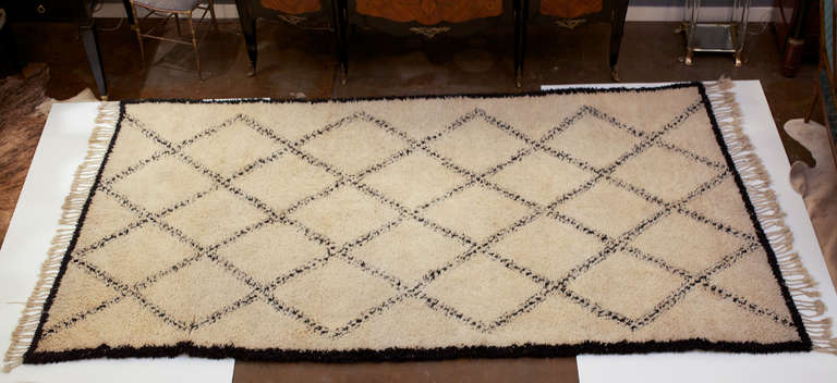 Handwoven Moroccan rug in lamb's wool with diamond pattern and braided tassels on both ends.
