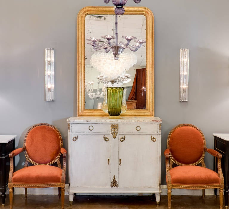 Italian pair of Murano glass and chrome sconces. Five crystal clear Murano glass lengths arranged in a semicircle with ridged chrome rings. Each sconce holds three medium base bulbs, and is wired to fit US standards.