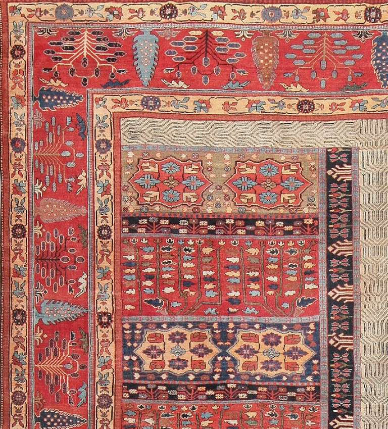 Truly a remarkable sight to behold, this majestic antique Persian garden carpet of Bakshaish design is a fantastic example of this prized and renowned style. This stupendous rug features an incredibly richly detailed, complex garden, separated by a