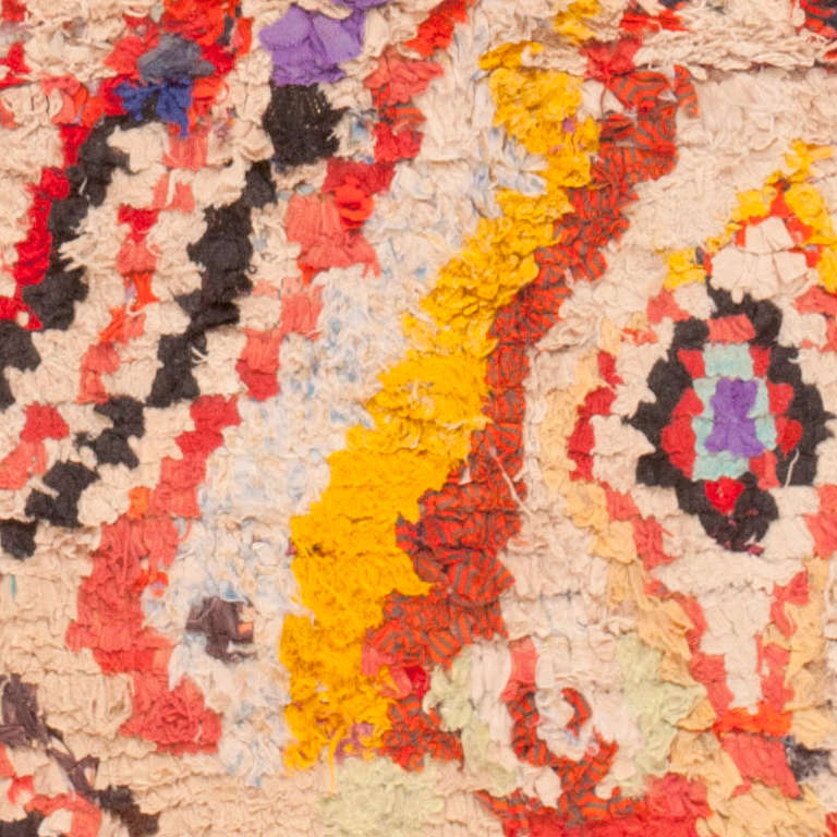 Created in Morocco, this vintage mid-century rug features a splendid variety of sumptuous textures and vivid rainbow hues. The boldly decorated field is comprised of formal large-scale lozenges surrounded by a colorful assortment of small-scale