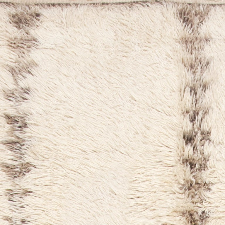 Moroccan rug, origin: Morocco, circa mid-20th century, created in Morocco, this sumptuous vintage rug features a luxurious plush ivory field reminiscent of shearling wool. Stacked pillars comprised of many tiny trilateral motifs create a powerful