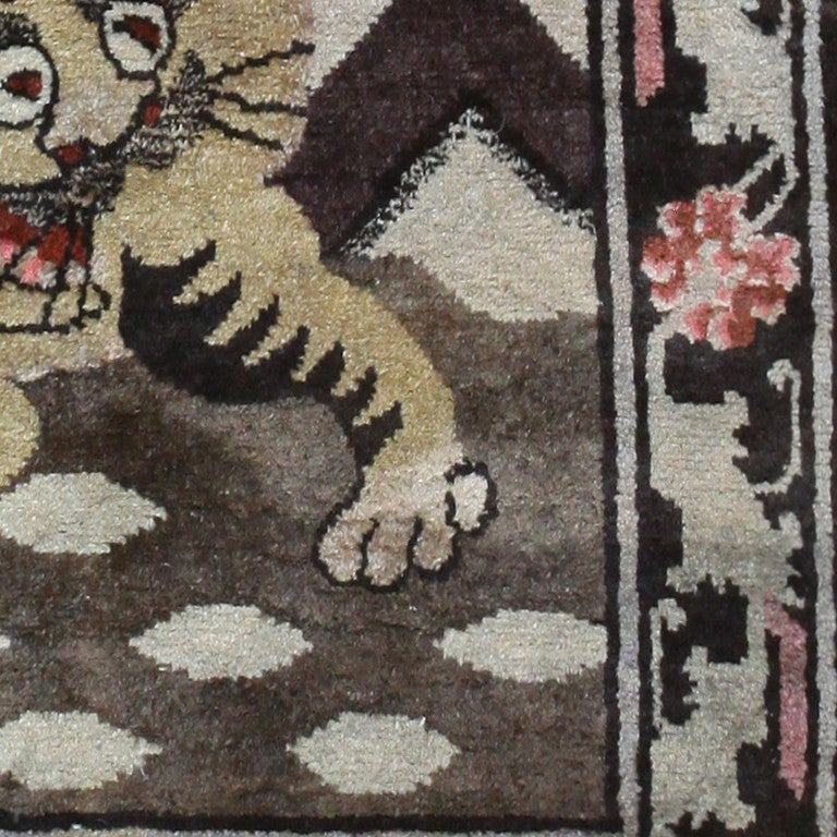 Antique tiger design rug, Tibet, 1920 -- A deep, crimson sky sets the ideal background for the white, snow-capped mountains before it in this Tibetan piece. Rich, earthy stone hues define the antique rug, from the mountainous backdrop to the rocky