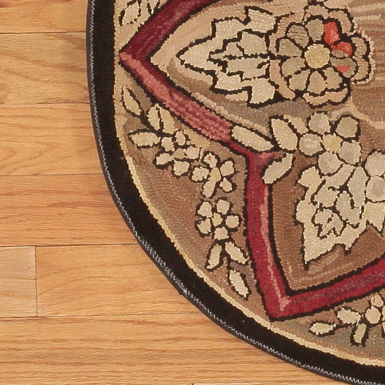 American hooked rug, circa 1900  A lovely curvilinear star pattern structures the field of this unusual circular antique American hooked rug. The floral clusters within it constitute the field while those outside it function as a kind of scalloped