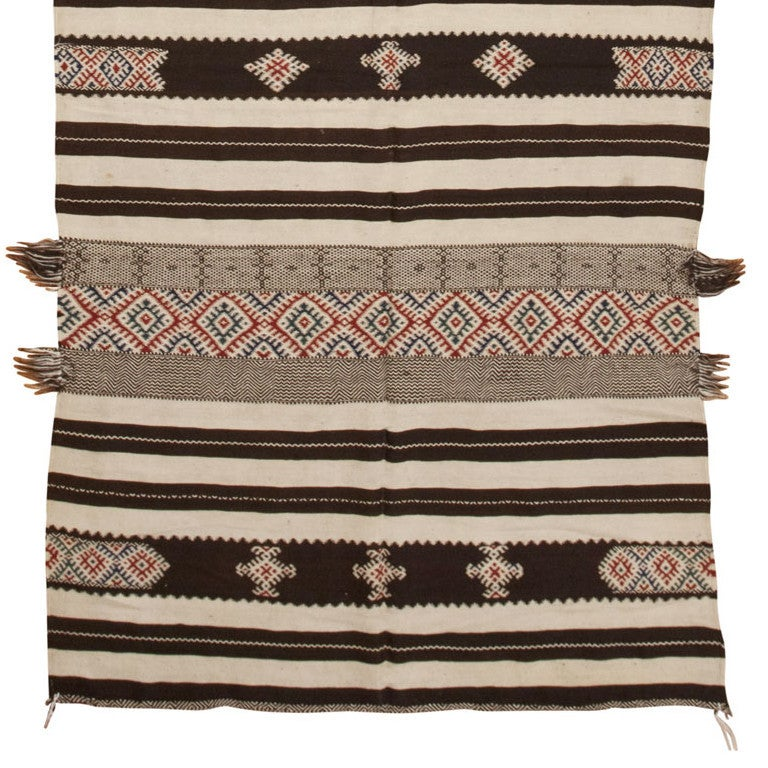 Created using ancient techniques, this traditional Kilim from Morocco features an outstanding variety of symbols and densely placed patterns rendered in a limited combination of deep walnut brown and ivory paired with cerulean blue and reddish