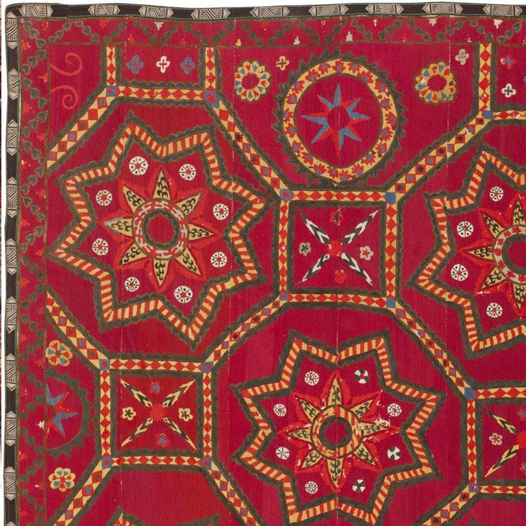 Created by Uzbekistani craftspeople, this exceptional antique Suzani masterpiece features a kaleidoscopic array of colors and geometric patterns rendered in an energetic folk art style. Based on traditional tile patterns and ancient geometric rules,