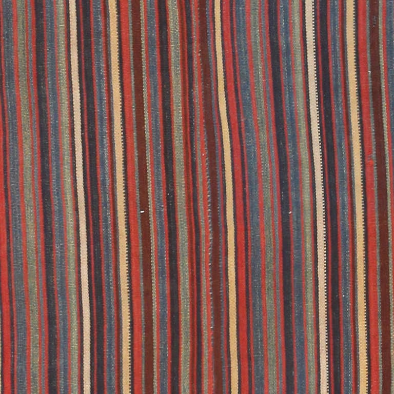 This dazzling Persian flat-weave jajim has an alluring, understated visage ideal for contemporary or traditional spaces. The handsome, earthy ground is traversed by an endless series of asymmetric stripes that are repeated at regular intervals. This