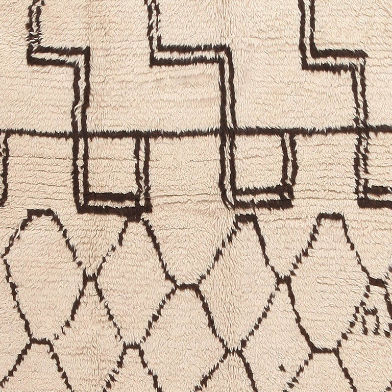 Representing the artful iconography of Morocco, this plush vintage mid-century rug is adorned with contrasting geometric figures that create a visual dichotomy. The striking composition centers on a delicate network of formal latticework tiles that