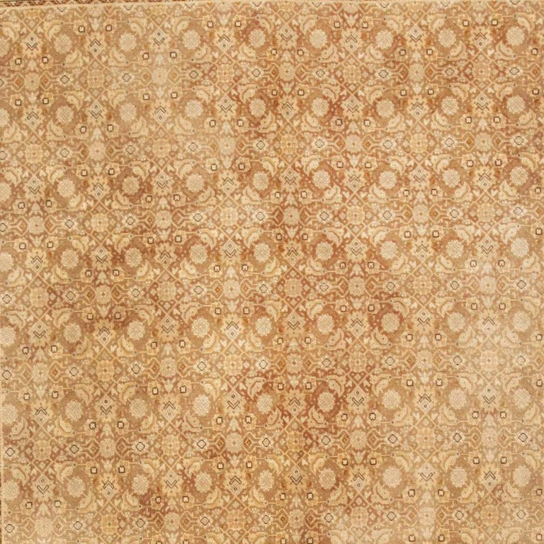 A complex Herati design in shades of tan and burgundy repeats in precise all-over symmetry across the rich cocoa ground of this lovely antique Tabriz.