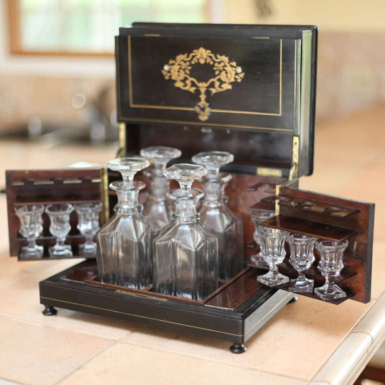An ebonized and hand-painted exterior opens to reveal a crystal service surrounded by polished rosewood. Four bottles with stoppers and seven glasses, late 19th-early 20th century.